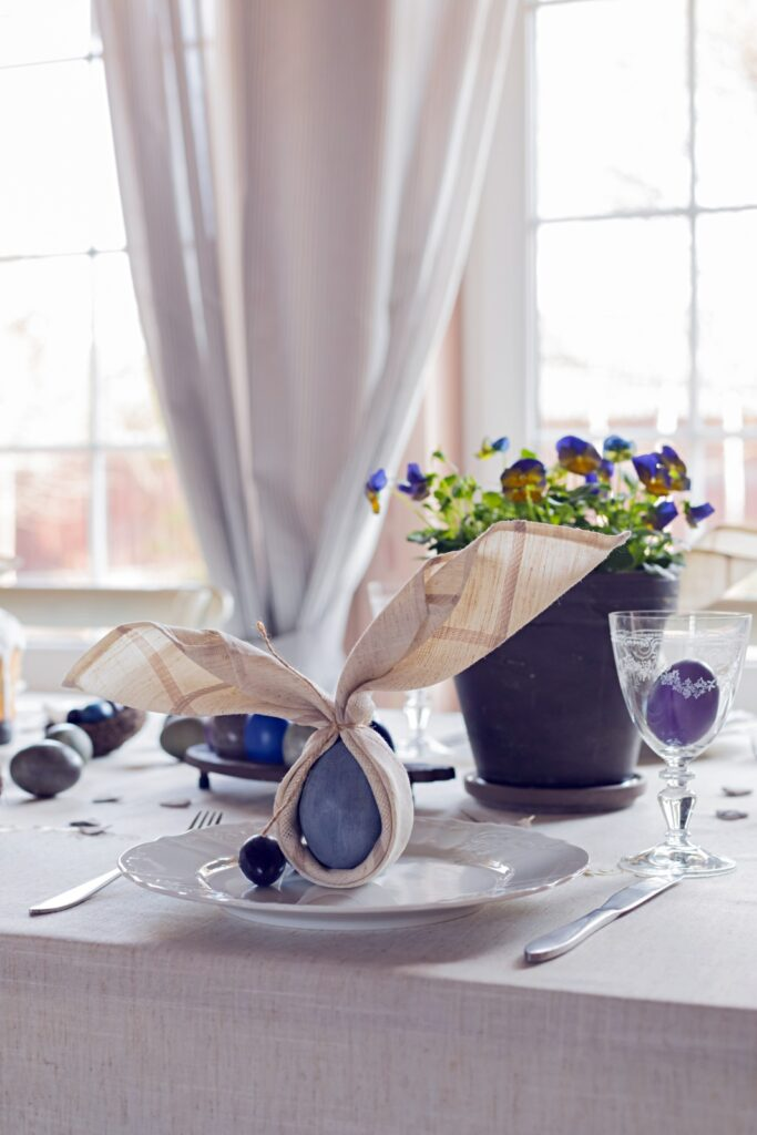 Easter table setting with blue eggs and potted violets