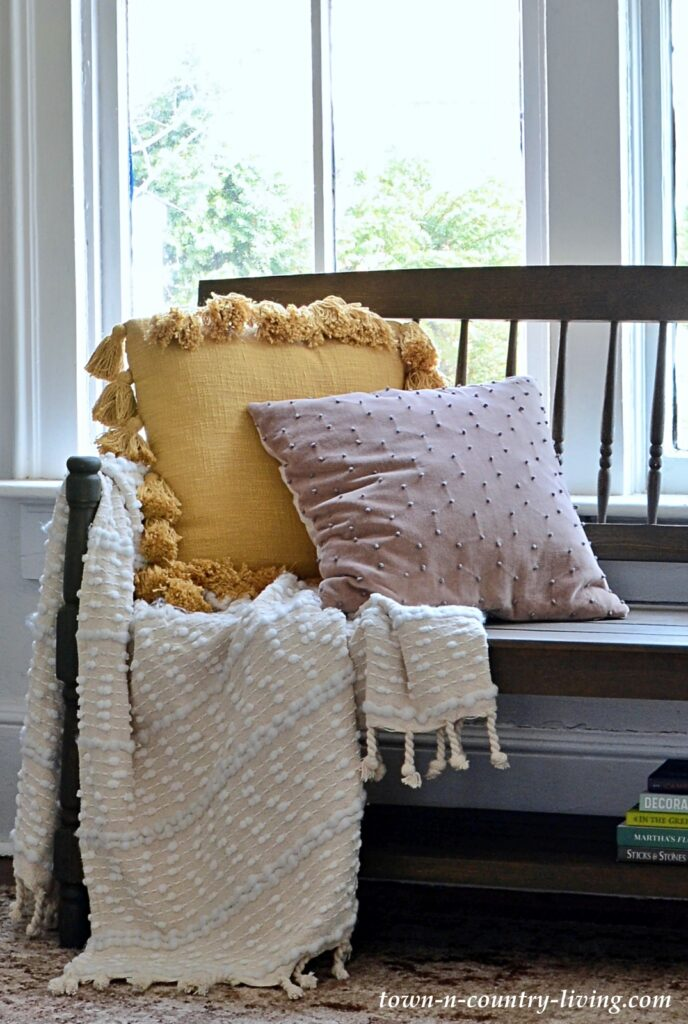 Textured Spring Pillows and Throw on a Wooden Bench