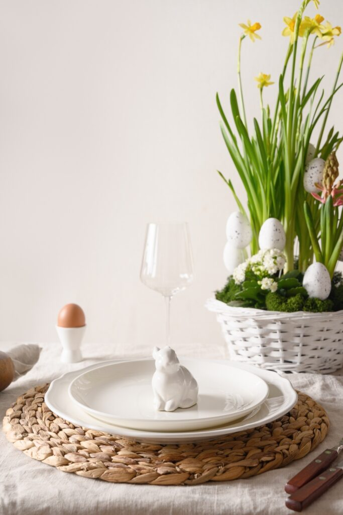 Spring Easter table setting with organic eggs, bunny and blossom flowers