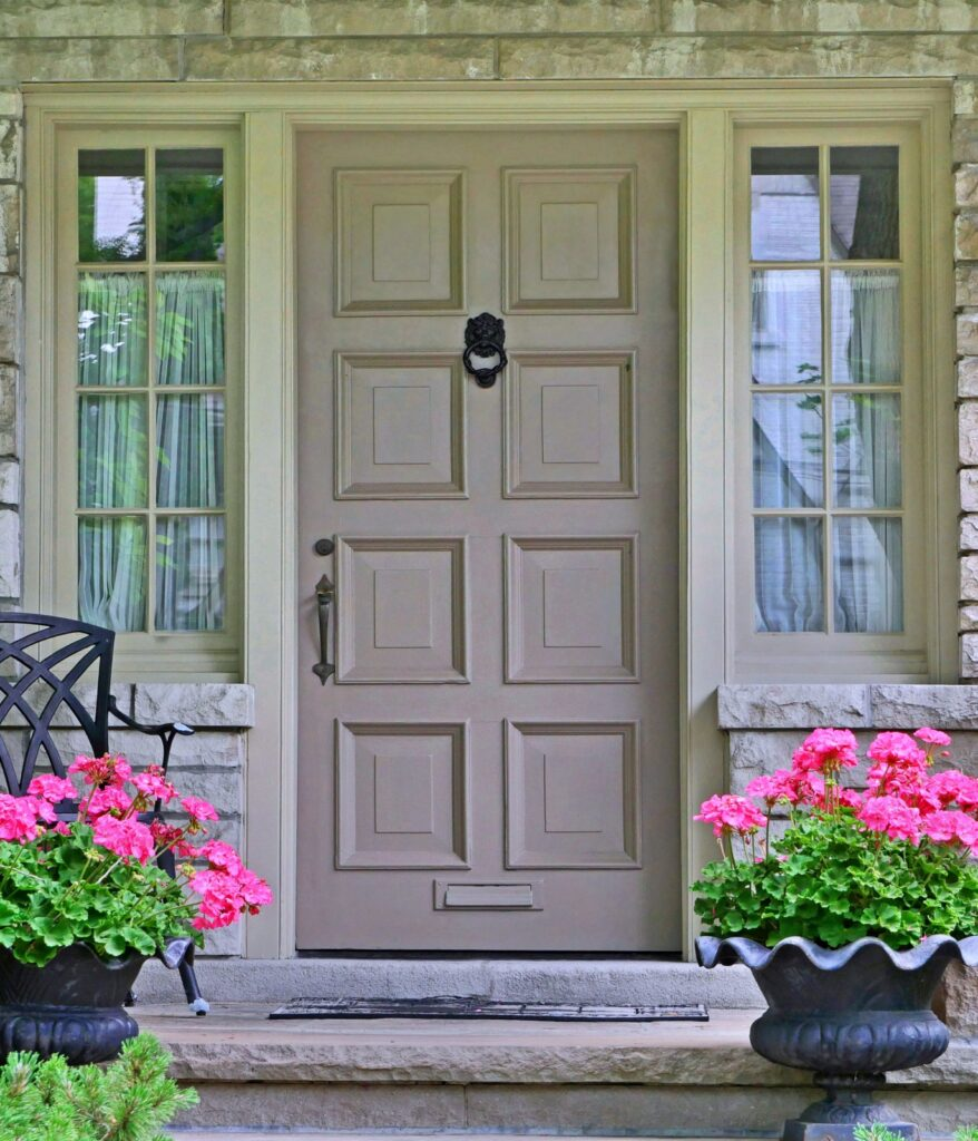 Tan Front Door with Potted Pink Geraniums