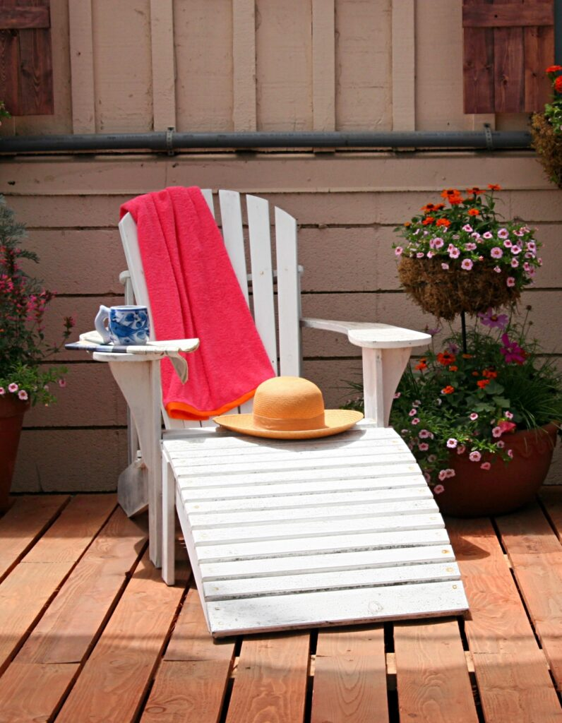 White Adirondack Chair on an Outdoor Deck with Flower Pots