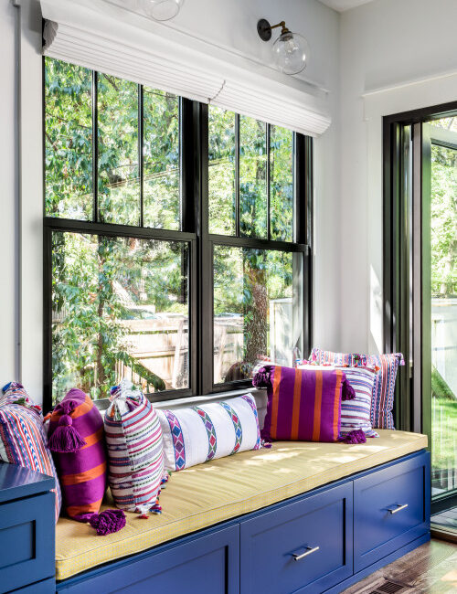Large farmhouse windows with dark blue window seat below