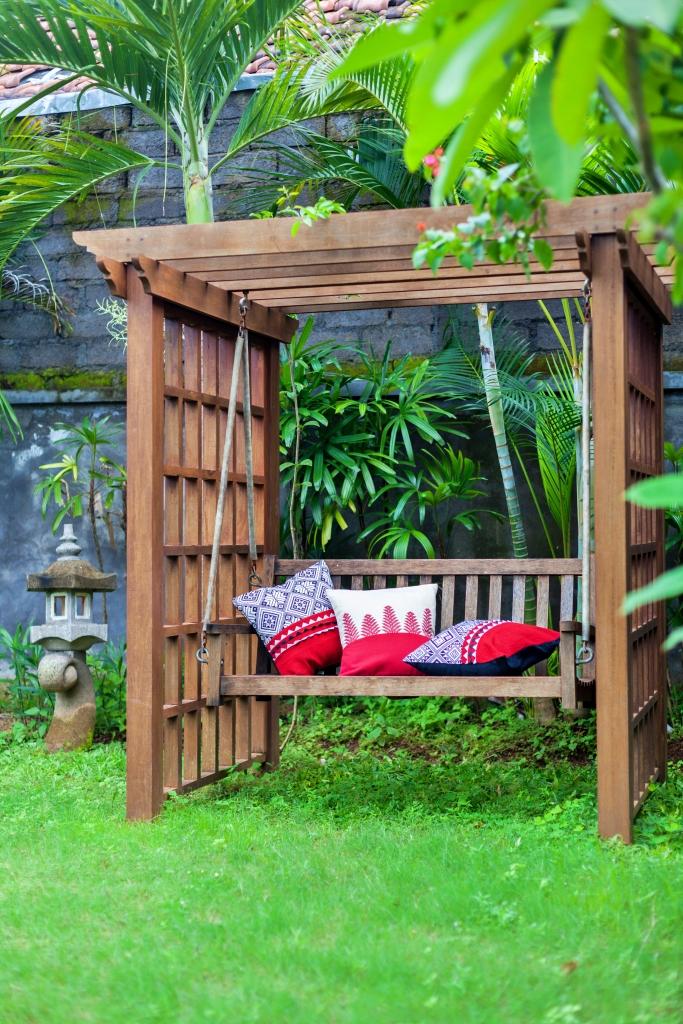 Klassische Holzschaukel im Freien im grünen Garten mit Kissen