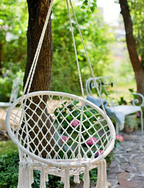 White macrame swing hanging in the garden