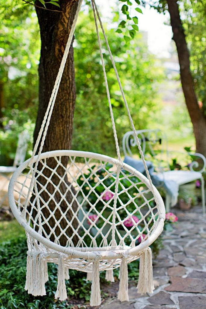 Weiße Makramee-Schaukel, die im Garten hängt