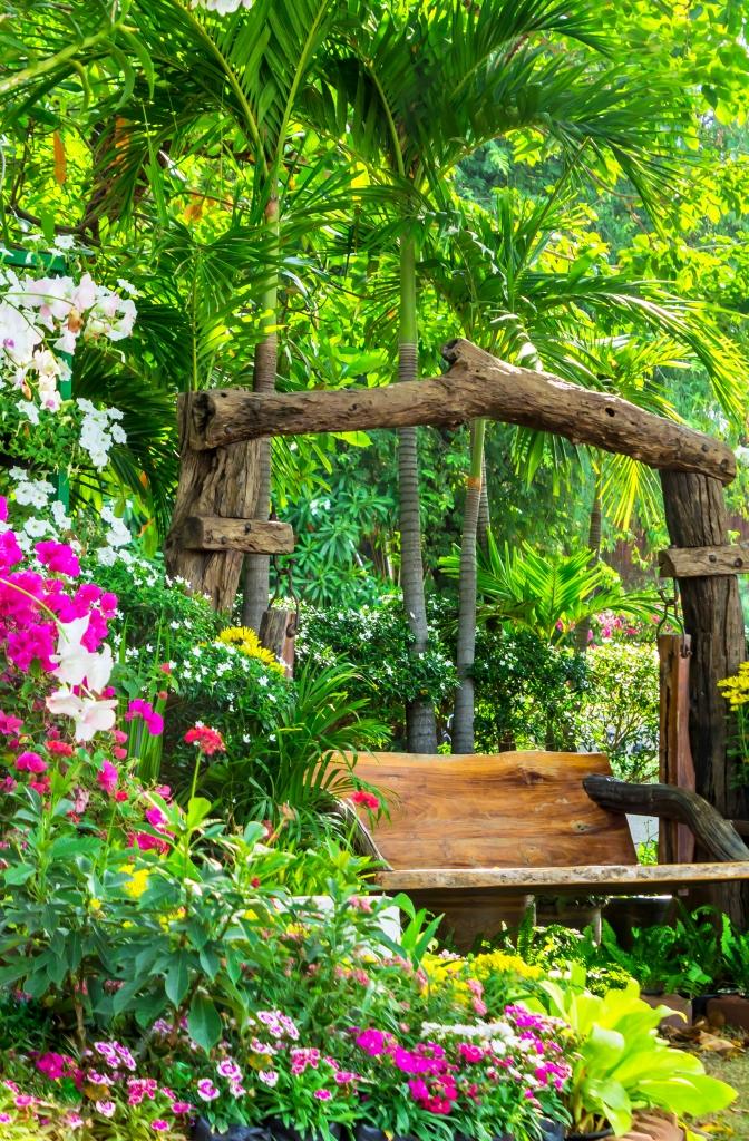 Holzschaukel in einem tropischen Garten