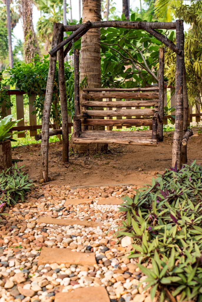 Rustikale Holzschaukel am Ende des Gartenweges