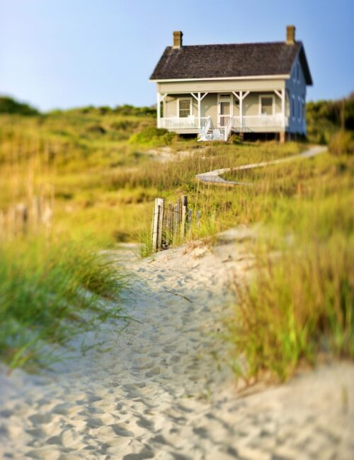 A sandy trail surrounded by brush leading up to a cottage on the beach.