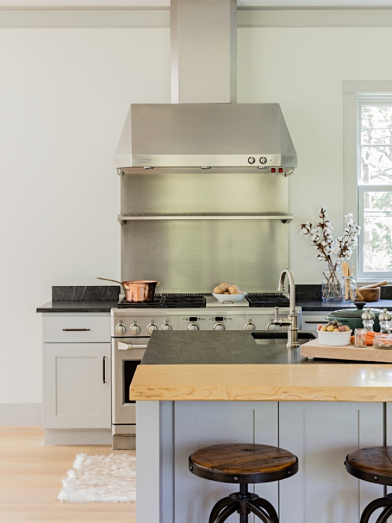 Stainless steel backdrop above a range in a Boston farmhouse kitchen