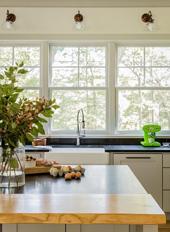 Trio of large windows above farmhouse kitchen sink
