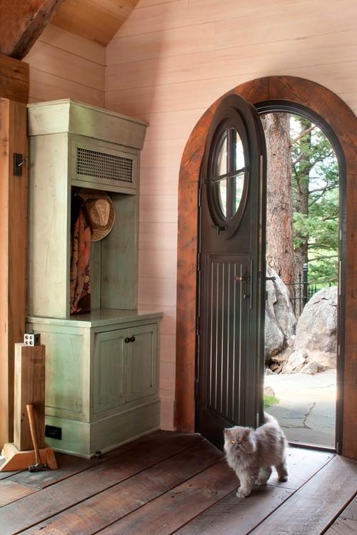 Arched front door with circle window leading into small stone cottage