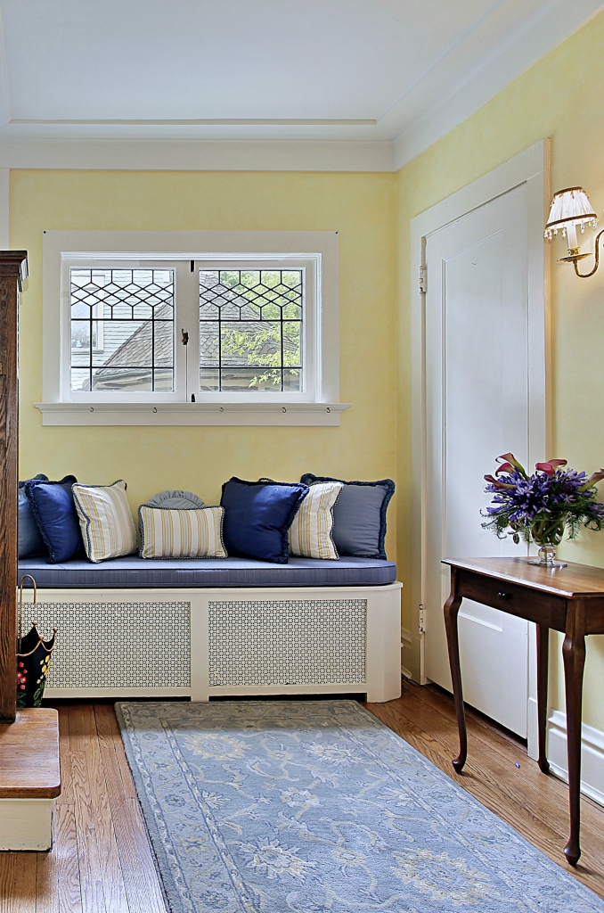 Eingangsbereich des Luxushauses mit gelben Wänden und blauen Kissen