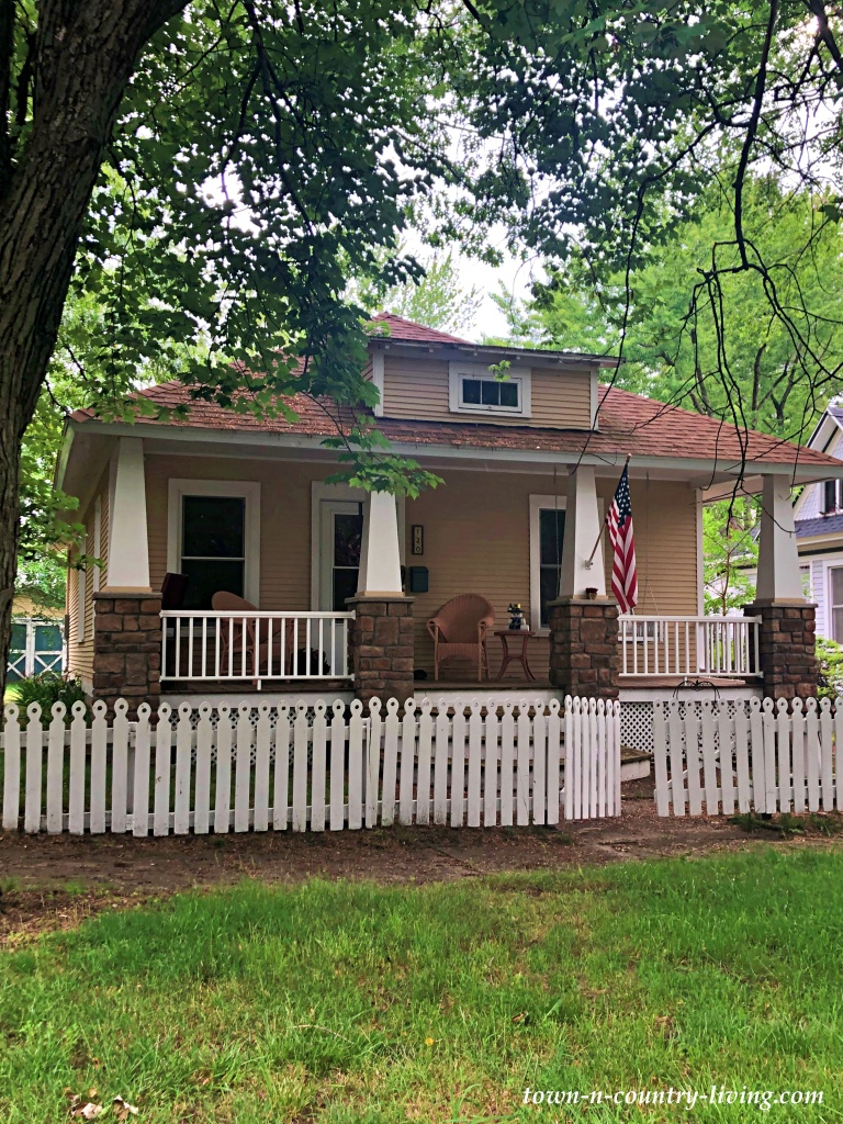 Cream-colored bungalow with front porch and white picket fence