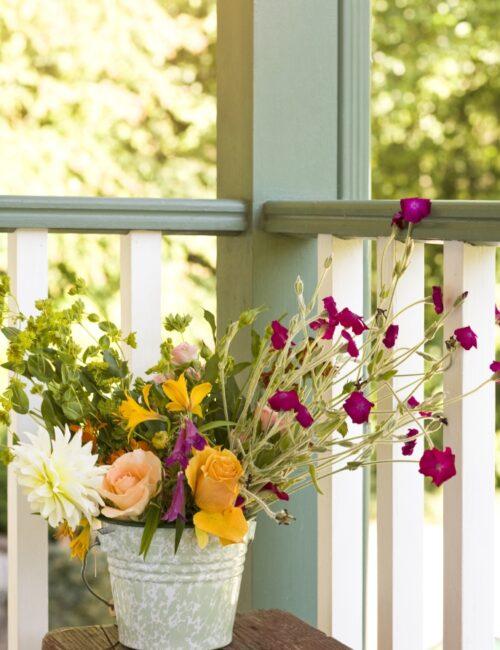 Casual flower arrangement bouquet in metal bucket on front porch.