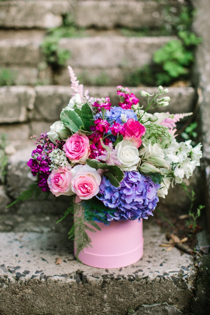 beautiful flowers and greenery in a pink box
