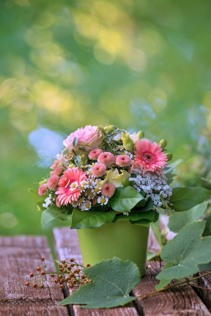 Colorful flower bouquet with gerbera daisies in green vase