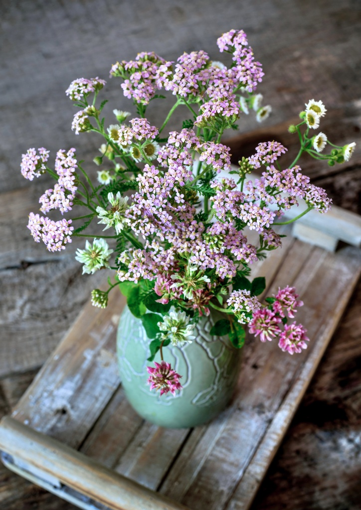 A bouquet in a vase of summer wild flowers on a wooden table