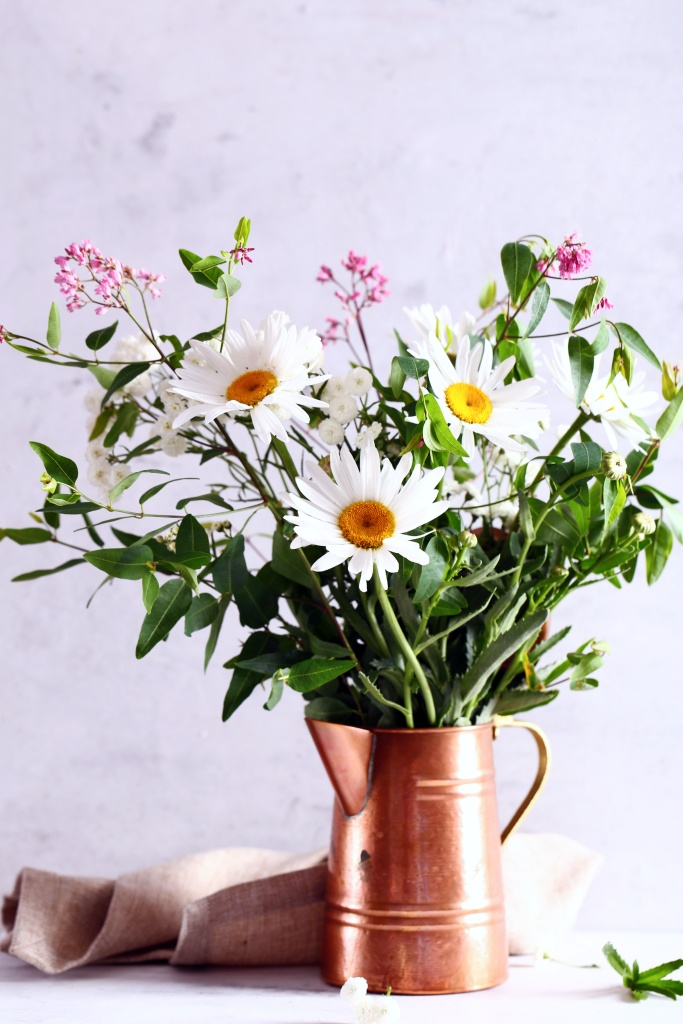 bouquet of daisies and wild wildflowers in brass pitcher