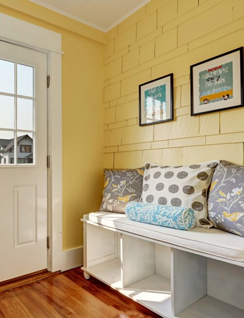 Entryway with yellow walls and storage bench in white with colorful pillows.