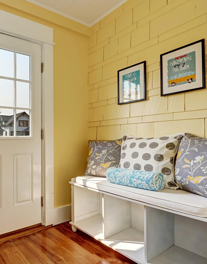 Eingang mit gelben Wänden und Aufbewahrungsbank in Weiß mit bunten Kissen.