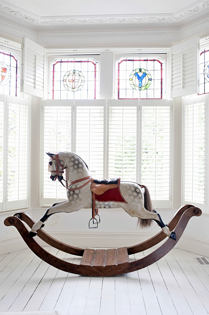 Antique rocking horse in bay window with stained glass