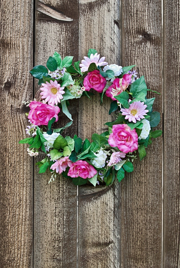 Floral wreath hanging on rustic wooden fence