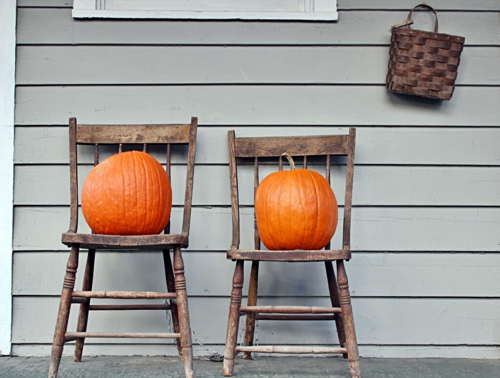 Vintage Chairs with Large Orange Pumpkins on a Fall Porch