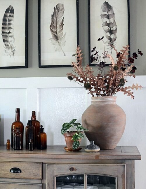Dining Buffet with Large Clay Pot and Vintage Brown Bottles