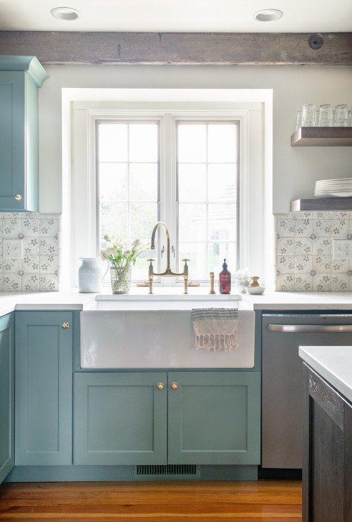 White apron sink beneath a country cottage kitchen window