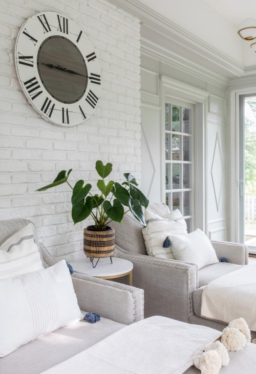 White airy sunroom with large wall clock and monstera plant