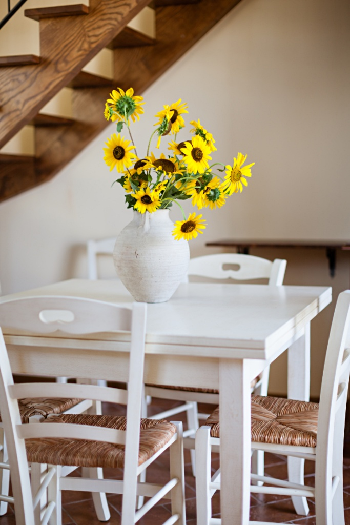 Bouquet of wild sunflowers on white kitchen table