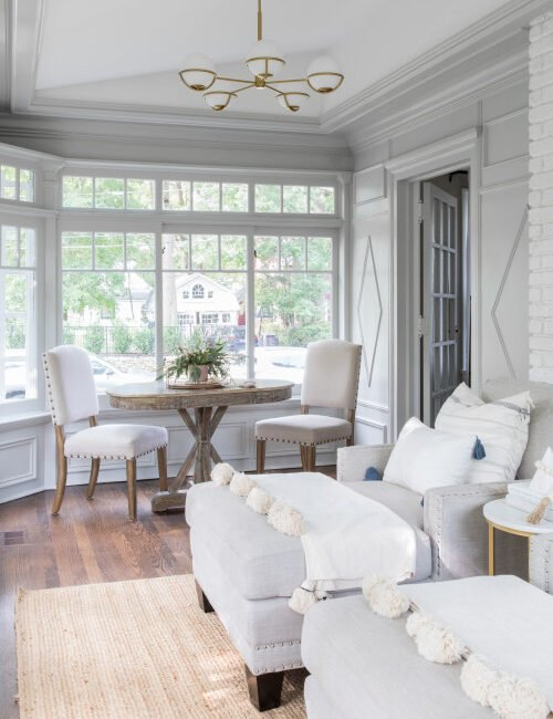 Architectural crown molding and trim work inside a white sunroom with matching lounge chairs