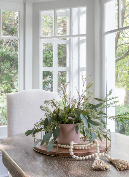 Simple centerpiece of faux greenery and wooden beads