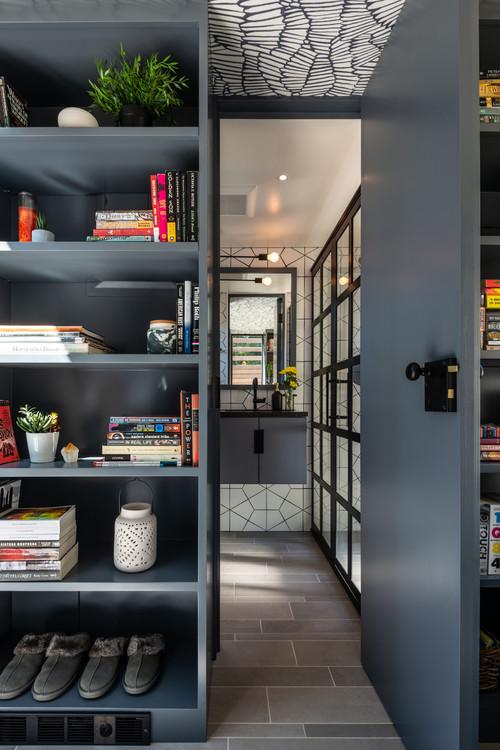 Door to bathroom between bookcases in a tiny house