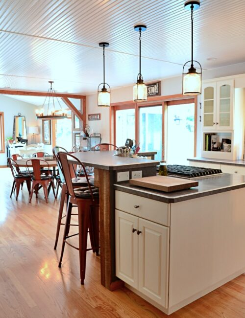 Large kitchen island with cooktop and red barstools in a farmhouse style kitchen