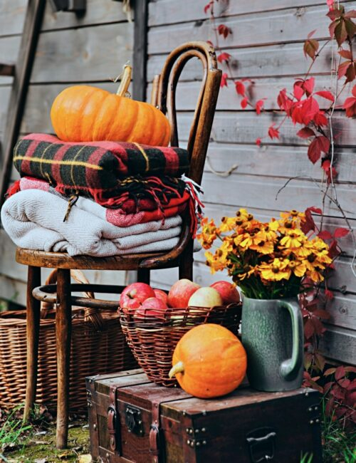 Bentwood chair on porch with plaid blankets, mums, basket of apples, and pumpkins
