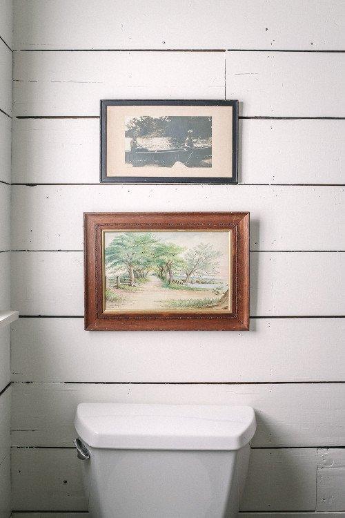 Vintage artwork in small bathroom with shiplap walls