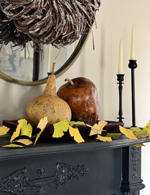 Decorate for fall by adding gourds and a leaf garland to a vintage mantel