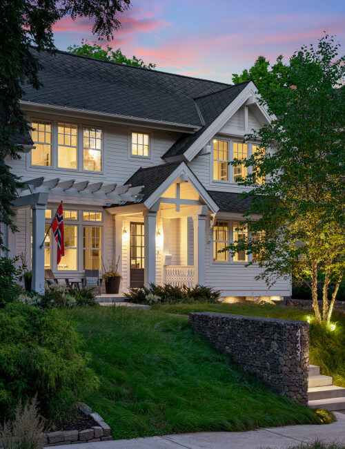 Transitional style white house at night with lights on
